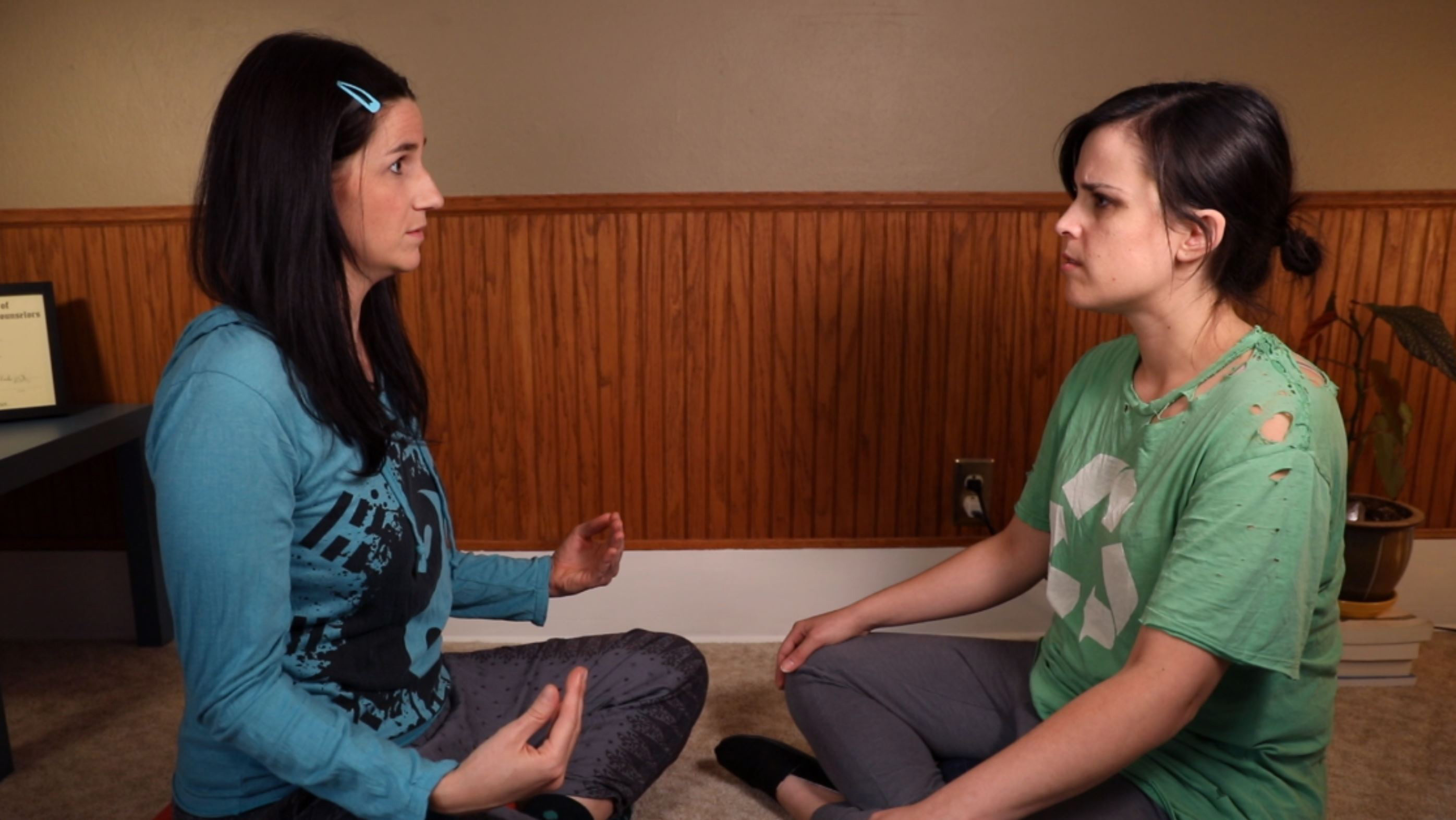 Still from Half-Quaked: Dr. Chameleon (Casey Pfeifer) leads Journalist Roberta Aguilar (Rochelle Muzquiz) in a frustrating meditation.